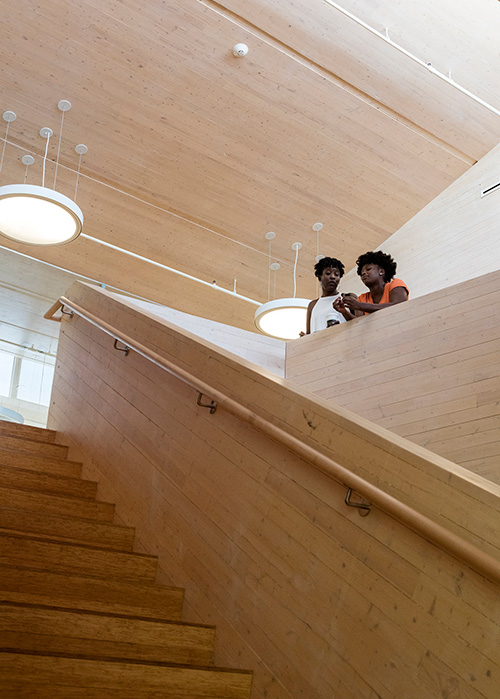 Two students stand in Common Ground High School in New Haven, CT, which was built with cross-laminated timber