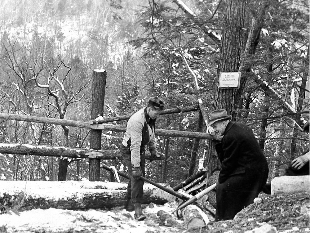 Milt Attridge (left) prepares to send a log down a log chute with NEFF founder Harris Reynolds